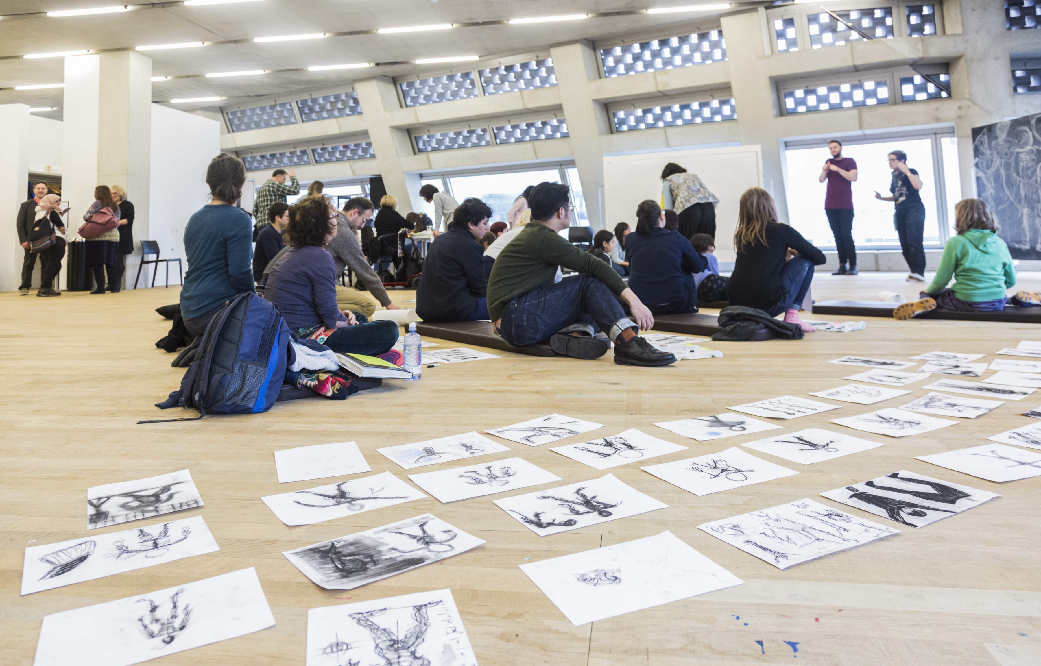 groups of people of varying ages, mostly seated on floor cushions, observe Rachel Gadsden as she leads n art workshop in front of a large blackboard with florid sketches on it