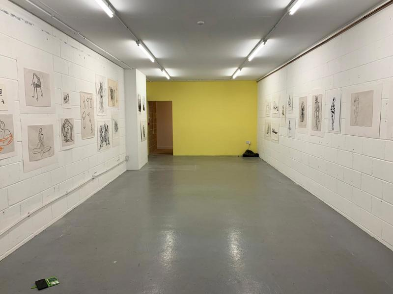 An exhibition space - image shows the two walls of a long room lined with Lauren