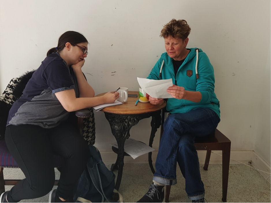 Two white women sit inside at a small table in front of a white wall. They are looking at a piece of white paper together with neutral expressions