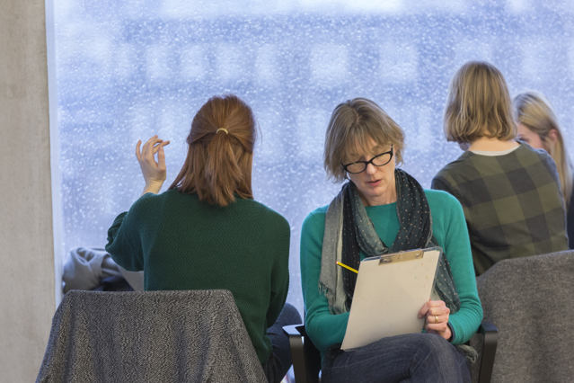 two women sit shoulder to shoulder drawing in an atmsphere of calm concentration