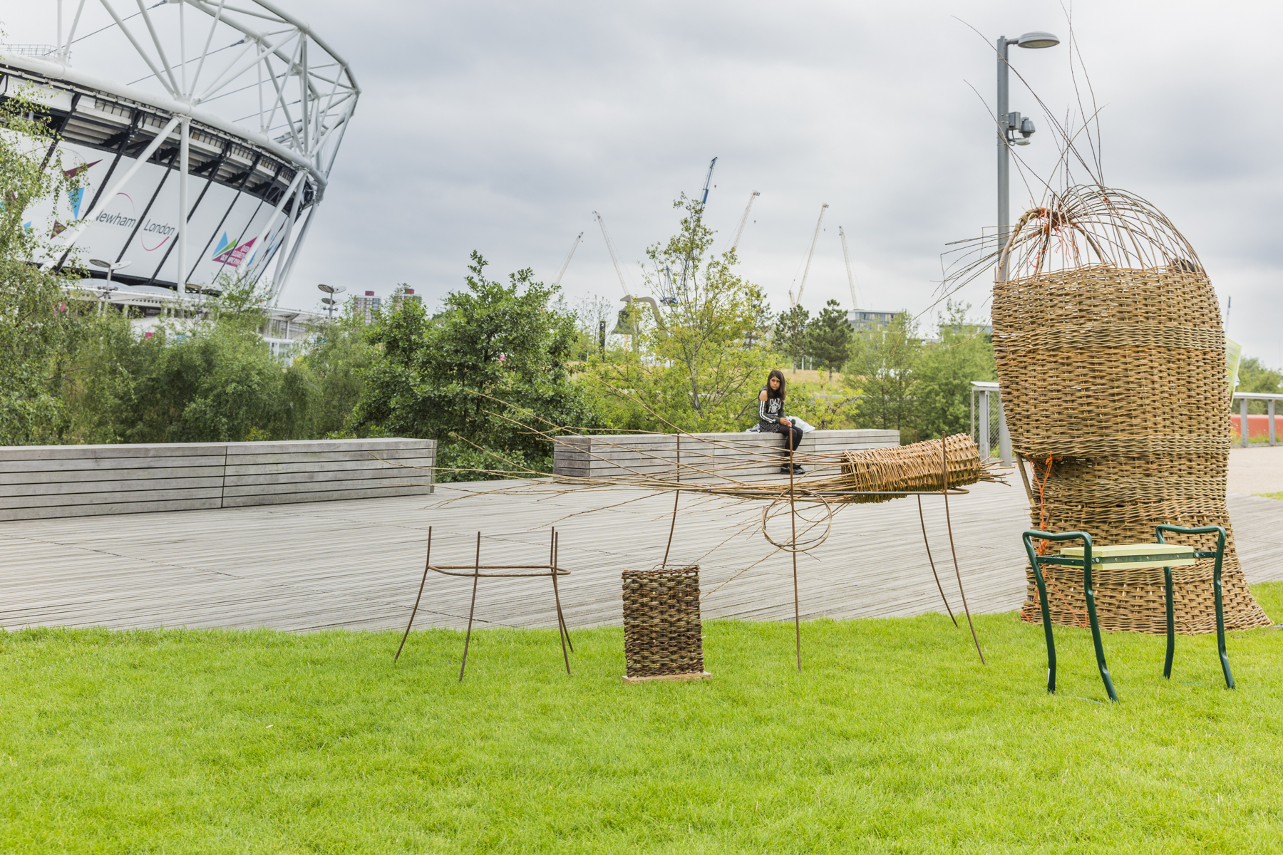 A collection of medium-sized sculptures woven from willow are standing in a park; there is a stadium in the background