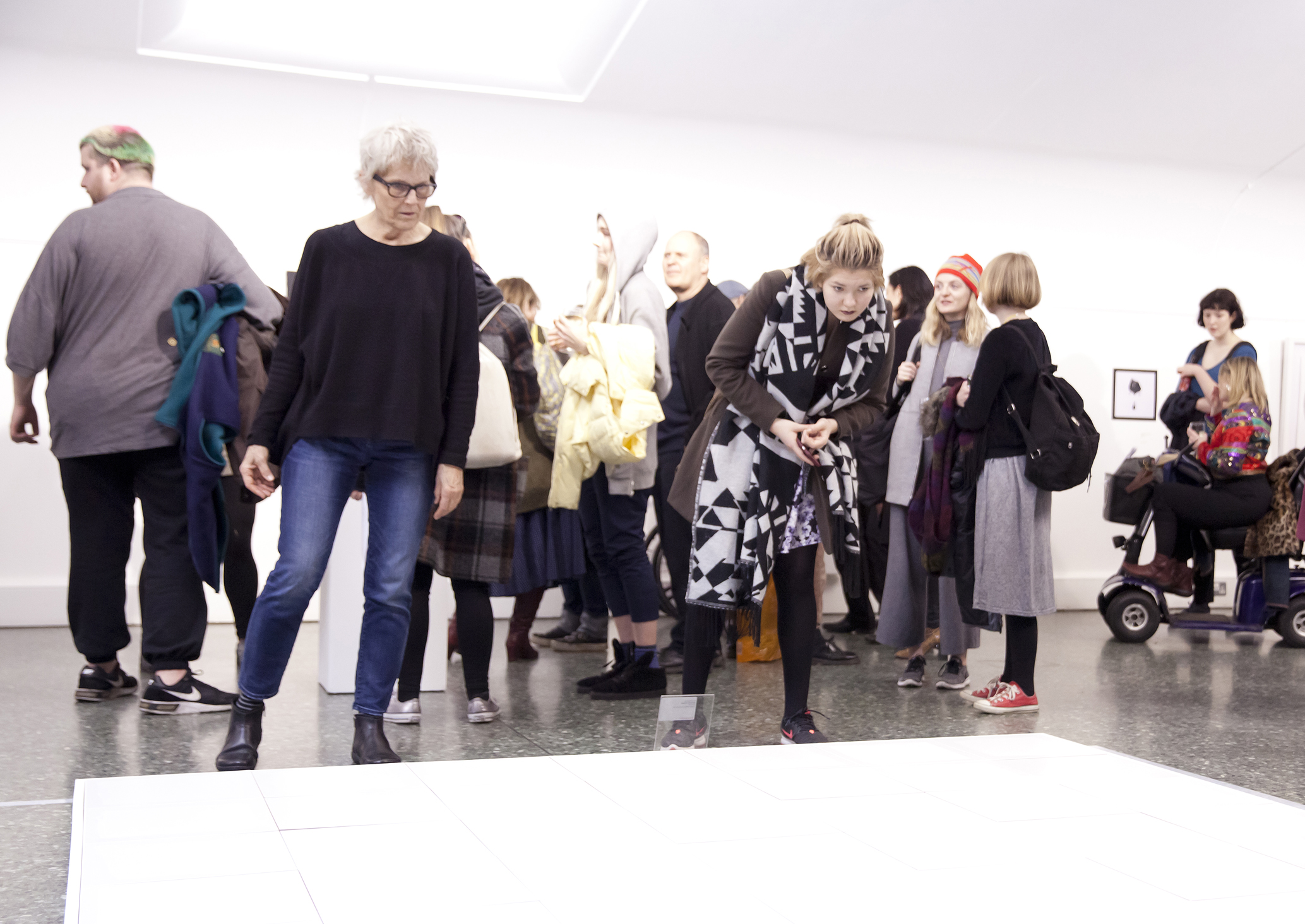 Members of the public looking at some of the artwork in the white gallery space