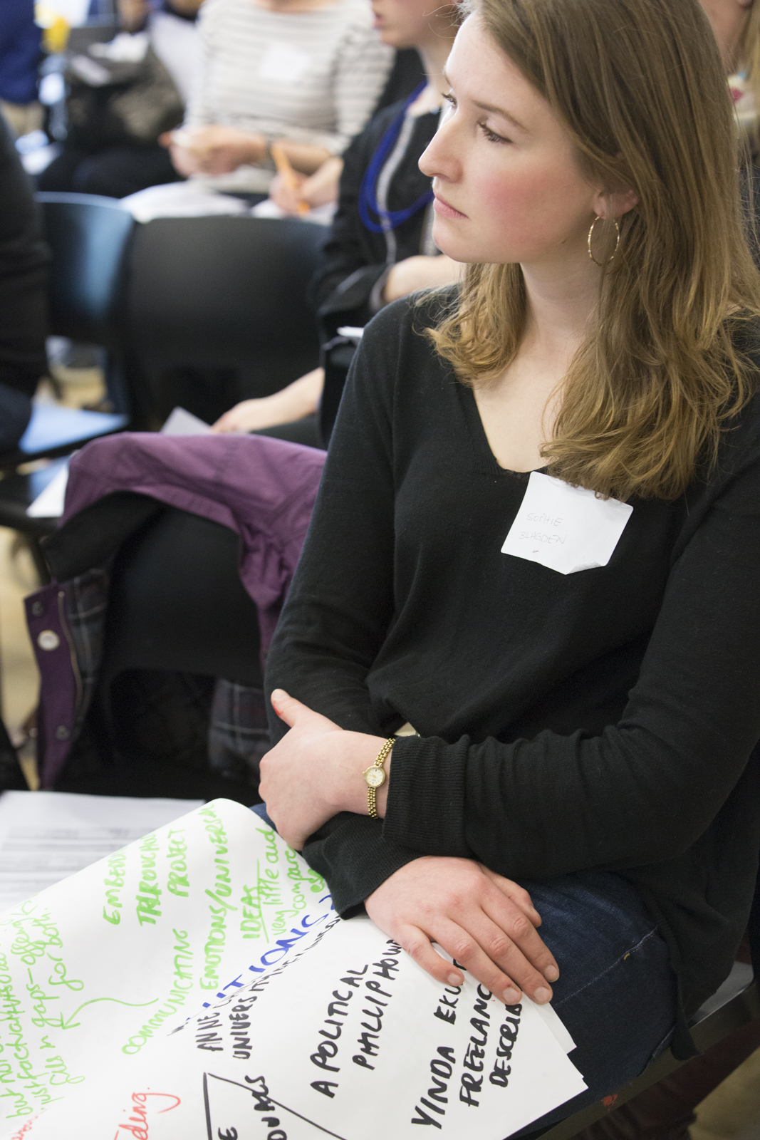 woman in a black top sits with a large sheet of notes from group discussions at Shape