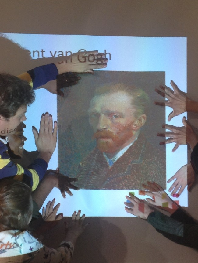 The young people framing a Vincent Van Gogh image with their hands.