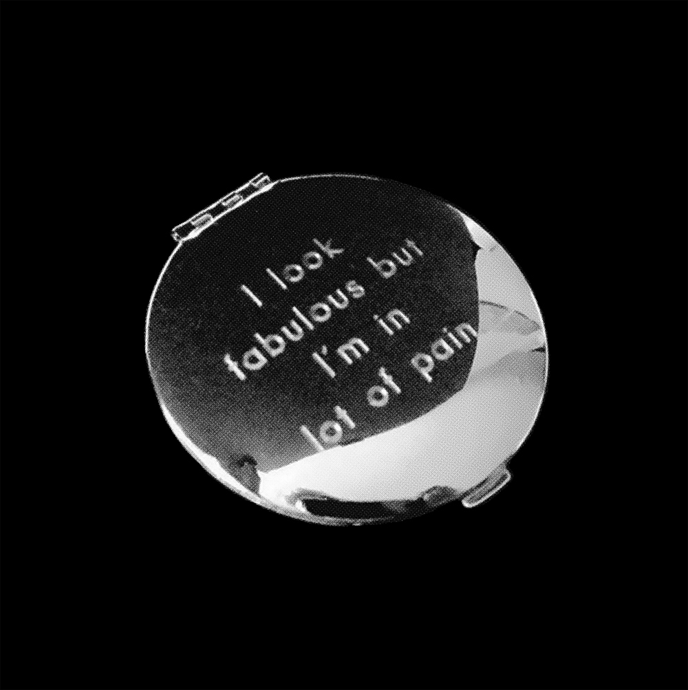 A silver compact mirror photographed from above on a black background. On the lid of the compact the words 'I look fabulous but I am in a lot of pain' are etched.