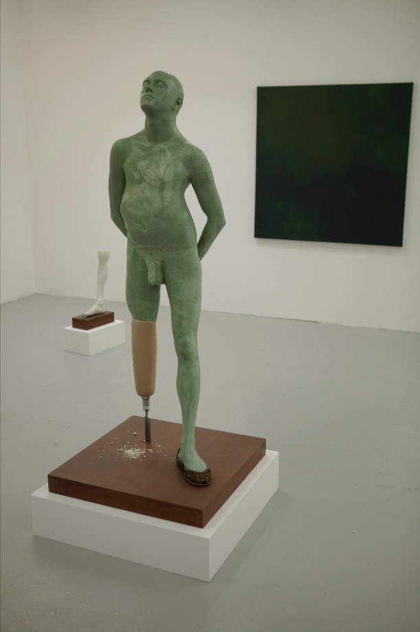 A green, realistic. life-size sculpture of a man with a wooden prosthetic leg is standing on a wooden plinth in a white-walled gallery room. The man is naked and his pose is defiant and proud, with his hands lightly clasped behind his back.