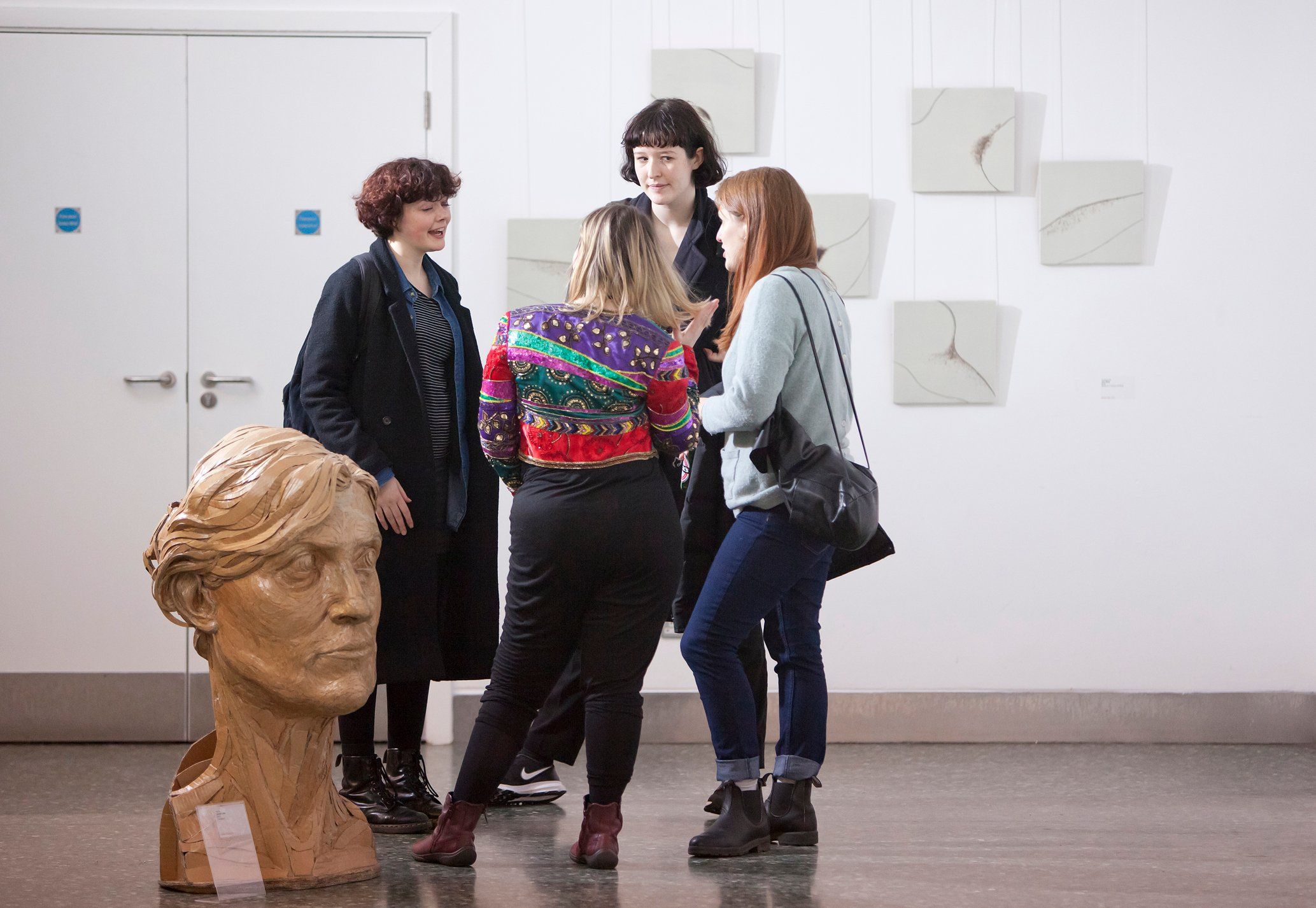 A large white room with people discussing art