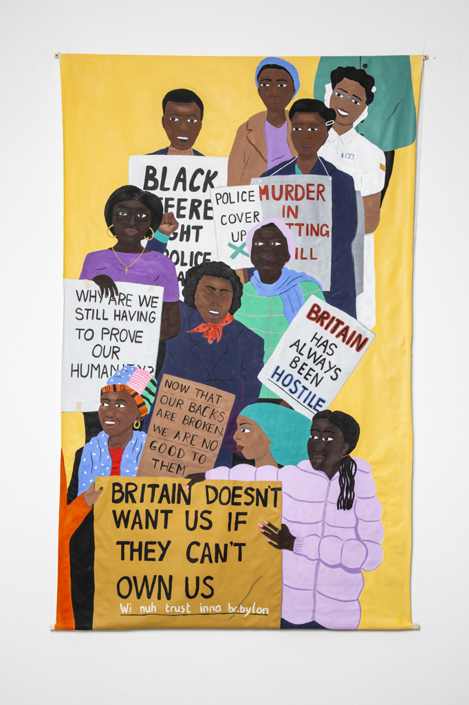 A line of 12 black women of differing ages marching towards the viewer, from the top right to bottom left corner of the composition. The women wear bright turquoise, pink, and navy blue clothing which contrasts beautifully against a bright yellow block background. Some hold banners. On which the text reads: 'Britain doesn