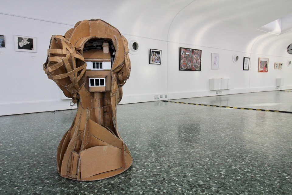 A large cardboard sculpture of the back a person's head stands on the floor of a gallery, with a row of pictures and paintings hanging behind it. The head is cut away at the back to reveal a small cardboard house inside.