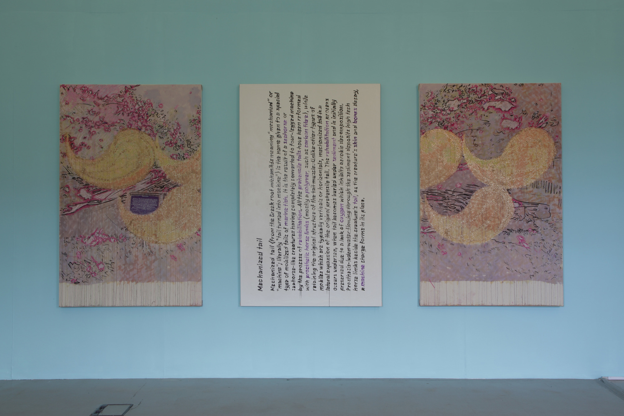 A triptych of large abstract paintings hanging on a blue wall. The two on either side are colourful and look like marbled paper; the central is white with illegible black text on it