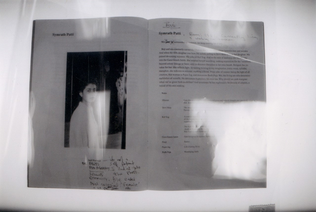 A black and white image of pages from a book under a plastic sheet on a white table