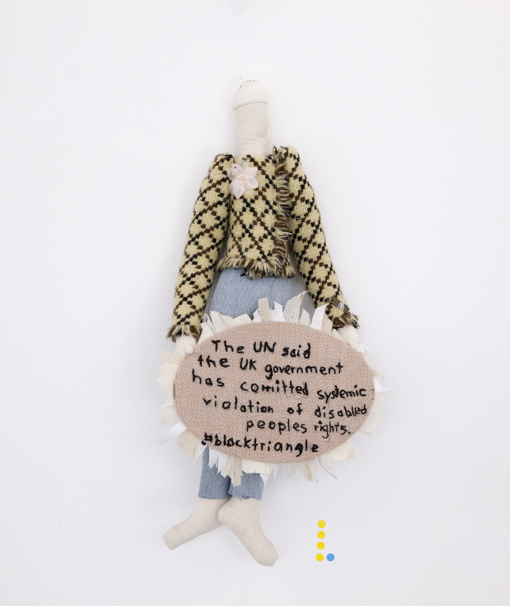 "A beige fabric rough-hewn human doll wearing clothes. It has a fabric badge pinned to it with the words ""The UN said the UK government has committed systemic violation of disabled people"