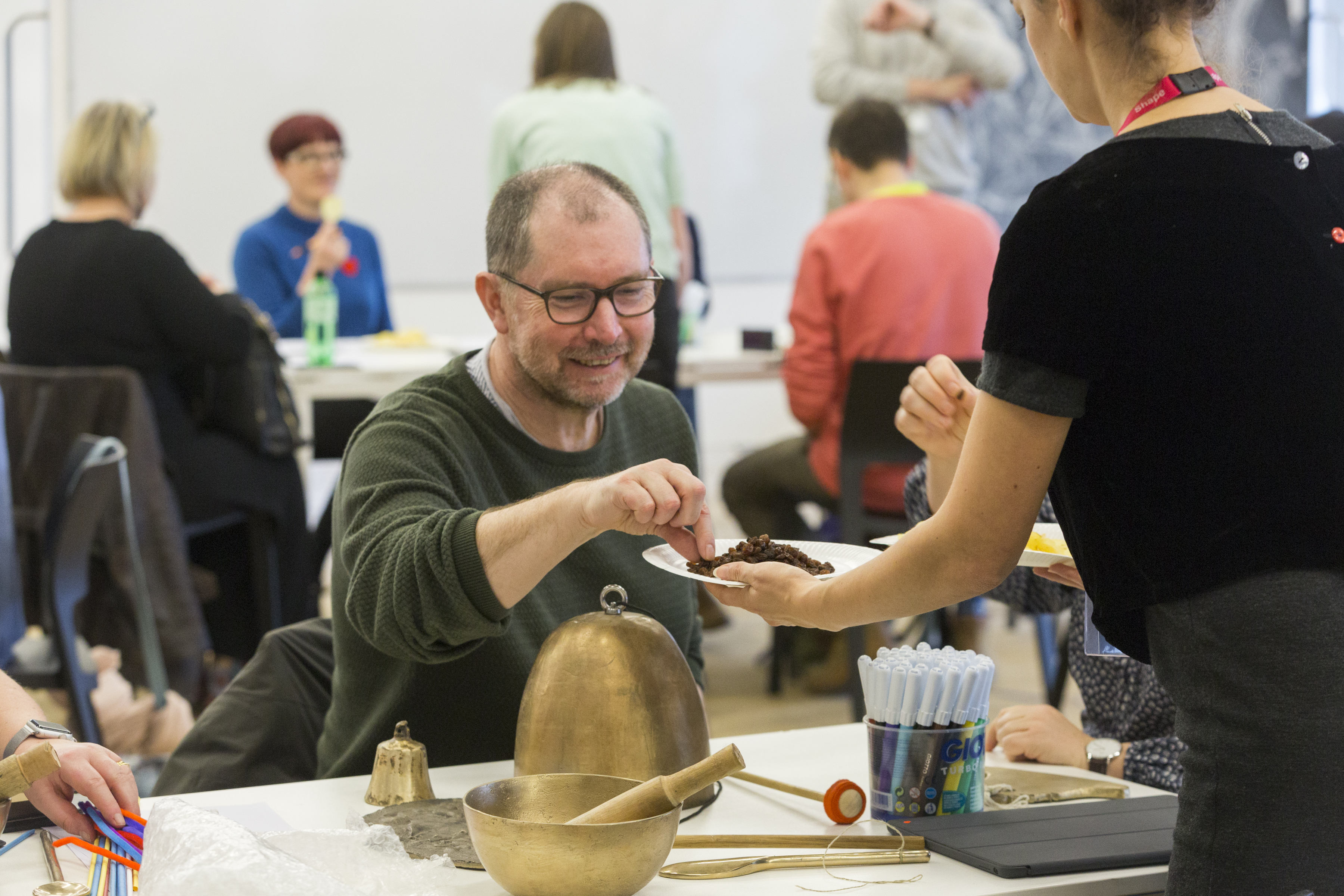 man leans forward whilst involved in aworkshop; the man is surrounded by other people, all of whom are using art materials in an atmosphere of enjoyable activity