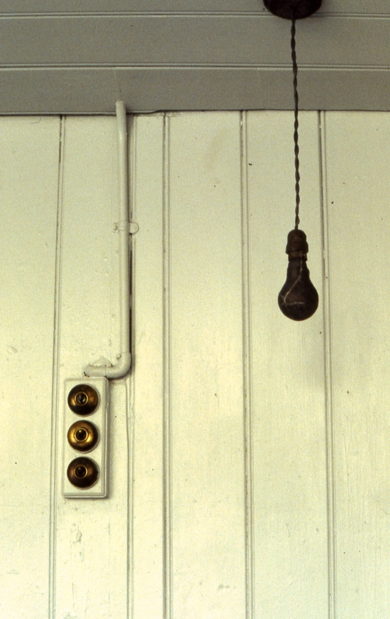 A fake black lightbulb on a wire, amde from lead, hangs from a ceiling in front of a white wall.