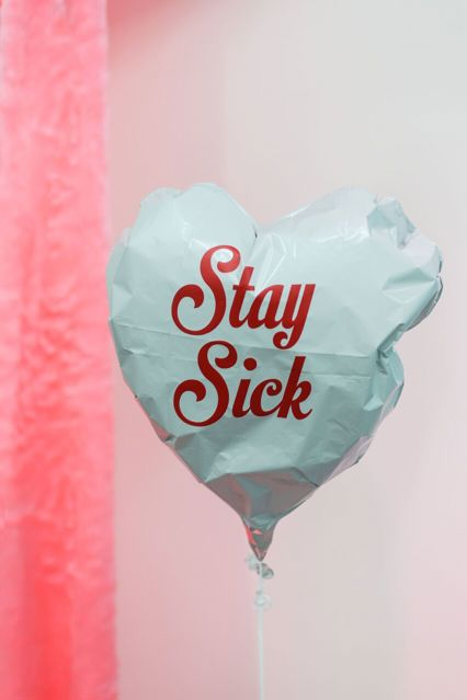 Photograph of part of an art installation. A white, heart-shaped balloon floats in the air attached by a thin cord. The balloon is partially deflated and crumpled-looking. Printed on it in red letters are the words: Stay Sick