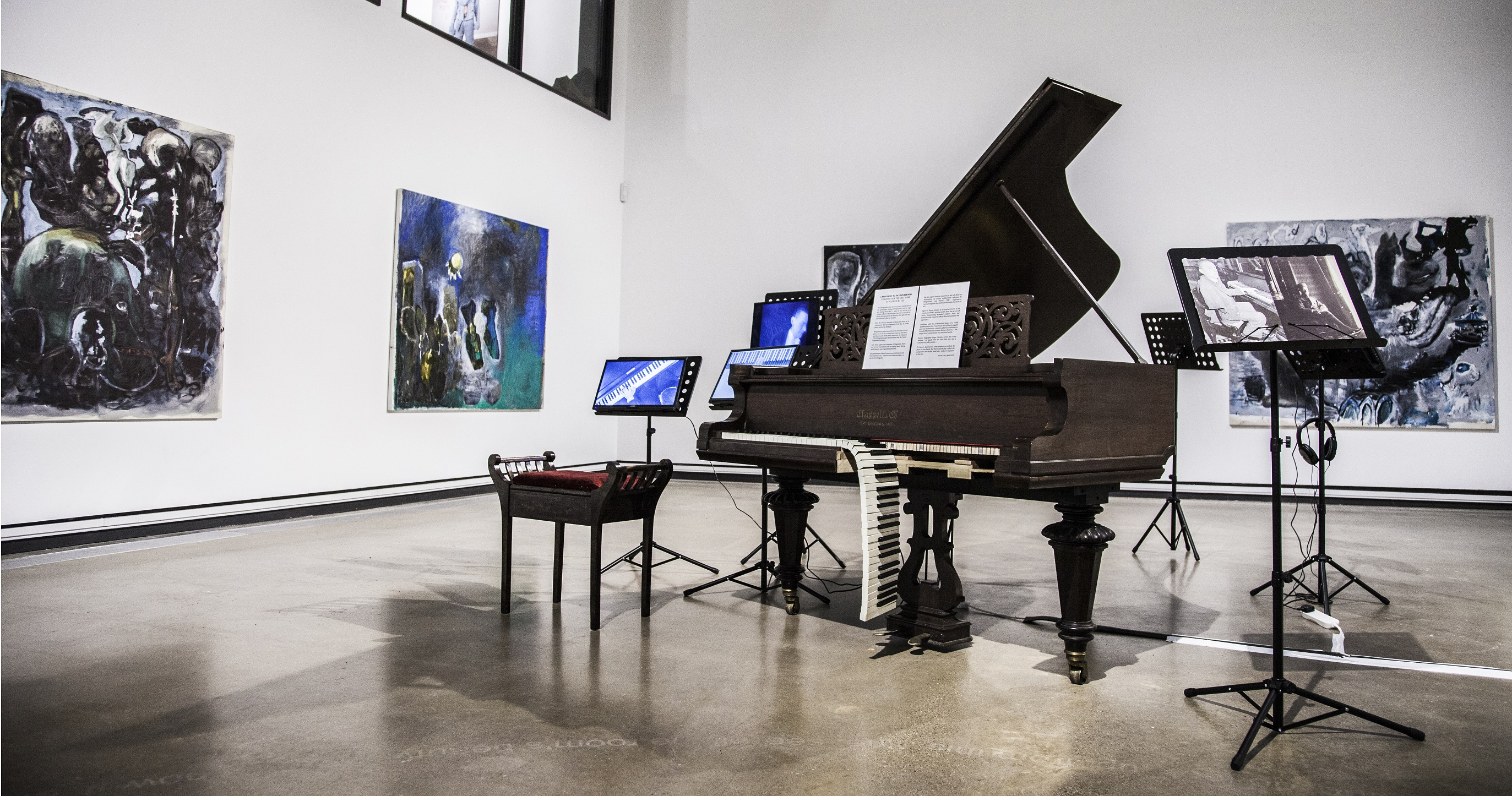 A black grand piano with half of the keys falling off sits in the middle of a very big, modern gallery space. There are screens on music stands around it and large, square abstract paintings on the walls behind it