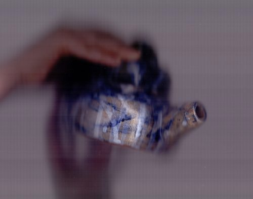 An image that forms part of the Centre of the Known Universe Project. It is a blurred and soft-focused image of a hand pouring from a teapot Letty has made.