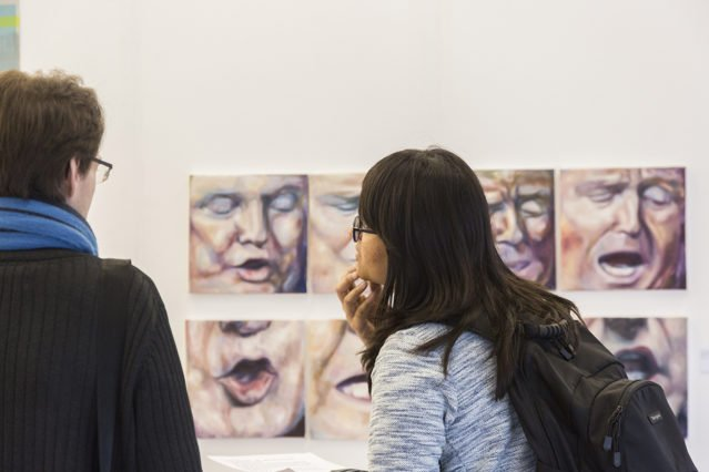 two people looking at the Shortlist art display at Tate exchange; the works they are paaign feature images of Donald Trump