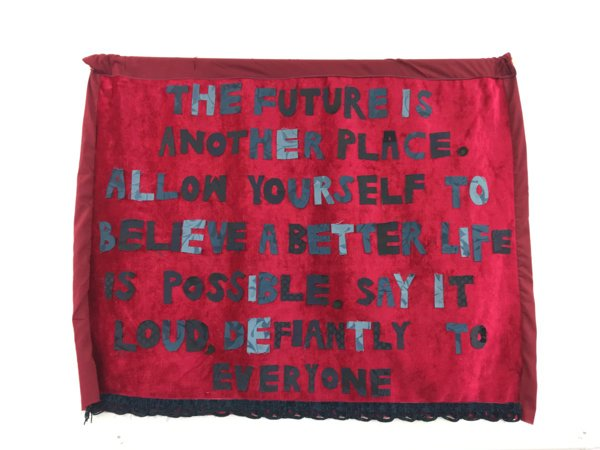A textile piece photographed as it hangs on a white wall. Upon a rich red backdrop of velvet fabric, with a rough hem around the edges, are appliqued words. The bold, capital letters are made from fabric in varying shades of grey. They have a hand-cut and sewn quality to them. They read: 'The Future is another place. Allow yourself to believe a better life is possible. Say it loud, defiantly to everyone.'