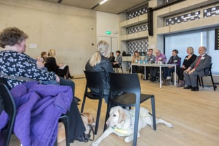 a seated woman with an assistance dog lying beneath her chair listens to the panel discussion at SHape