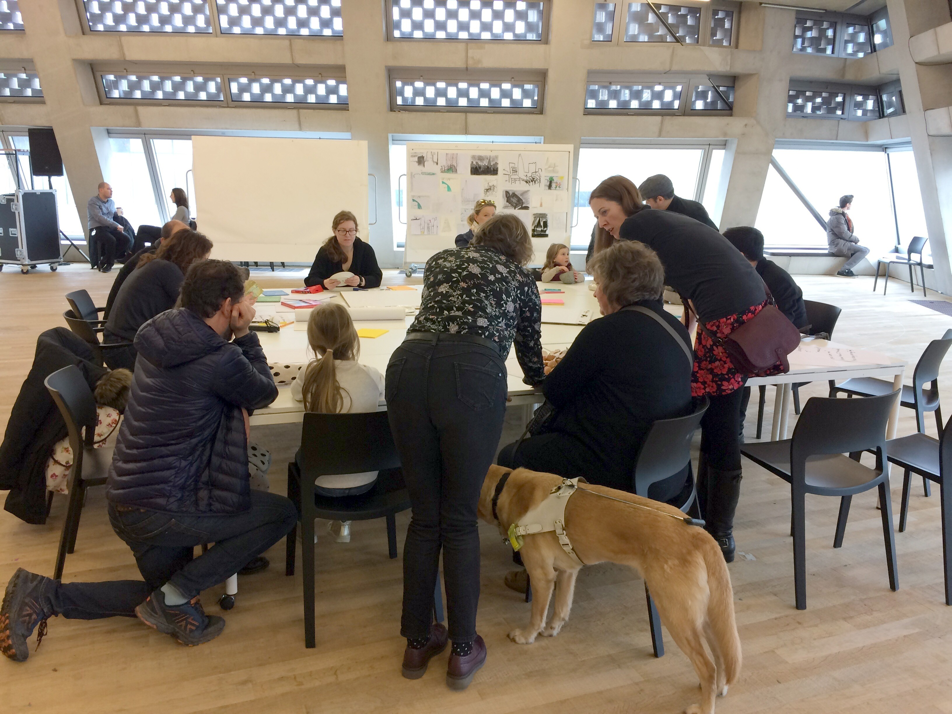 participants crowd around a table on which objects have been set out; an assistance dog indicates at least one of the participants is blind