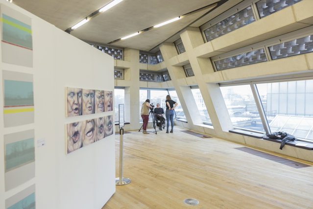 wide-angled view of the art showcase at tate exchange; in the background two women are interviewing a man in a wheelchair (recognisable as Tony Heaton OBE)
