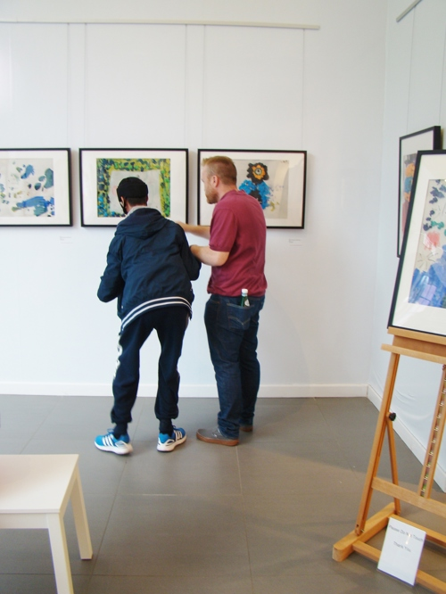 Student and teacher viewing artwork at the private view.