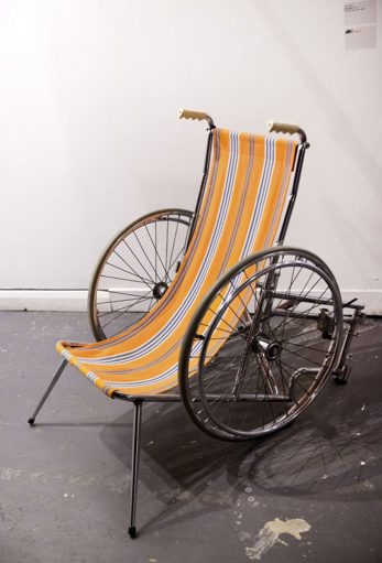 a manual wheelchair converted to resemble a deck chair with an orange and white striped  canvas seat
