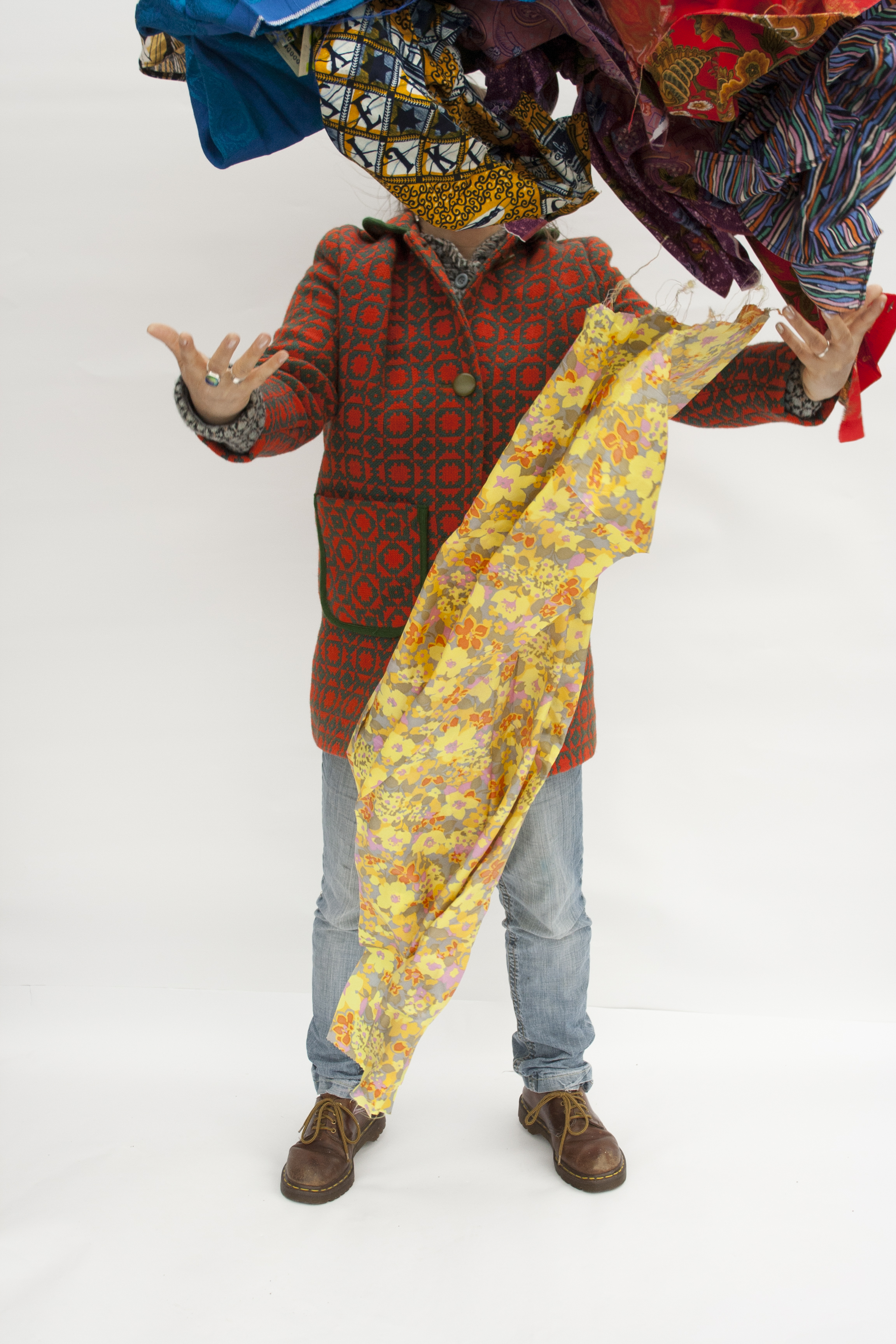 A person stands on an all white background with arms stretched towards the viewer. They are wearing a red shirt and blue jeans with a yellow fabric sash wrapped around them, and their had is obscured by more pieces of fabric in bright colours which h