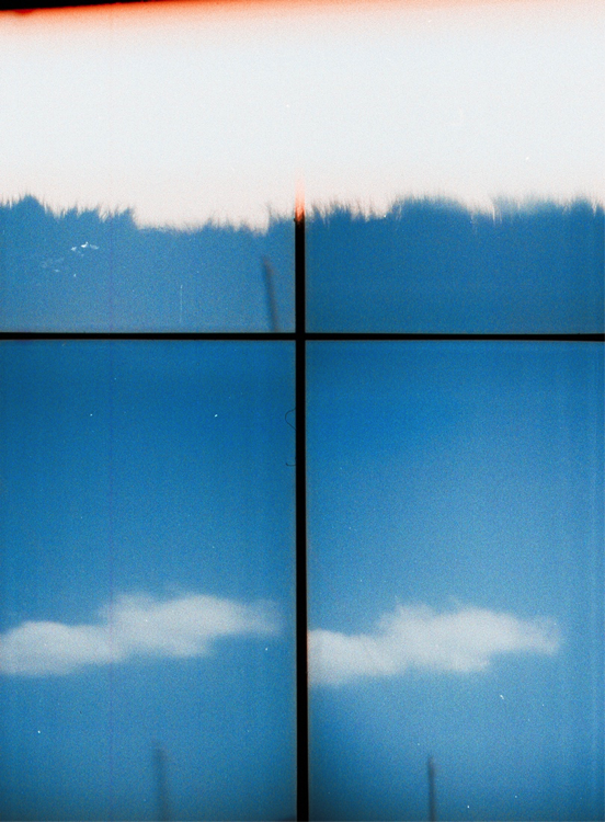 Analogue photography work of a blue sky with white patches