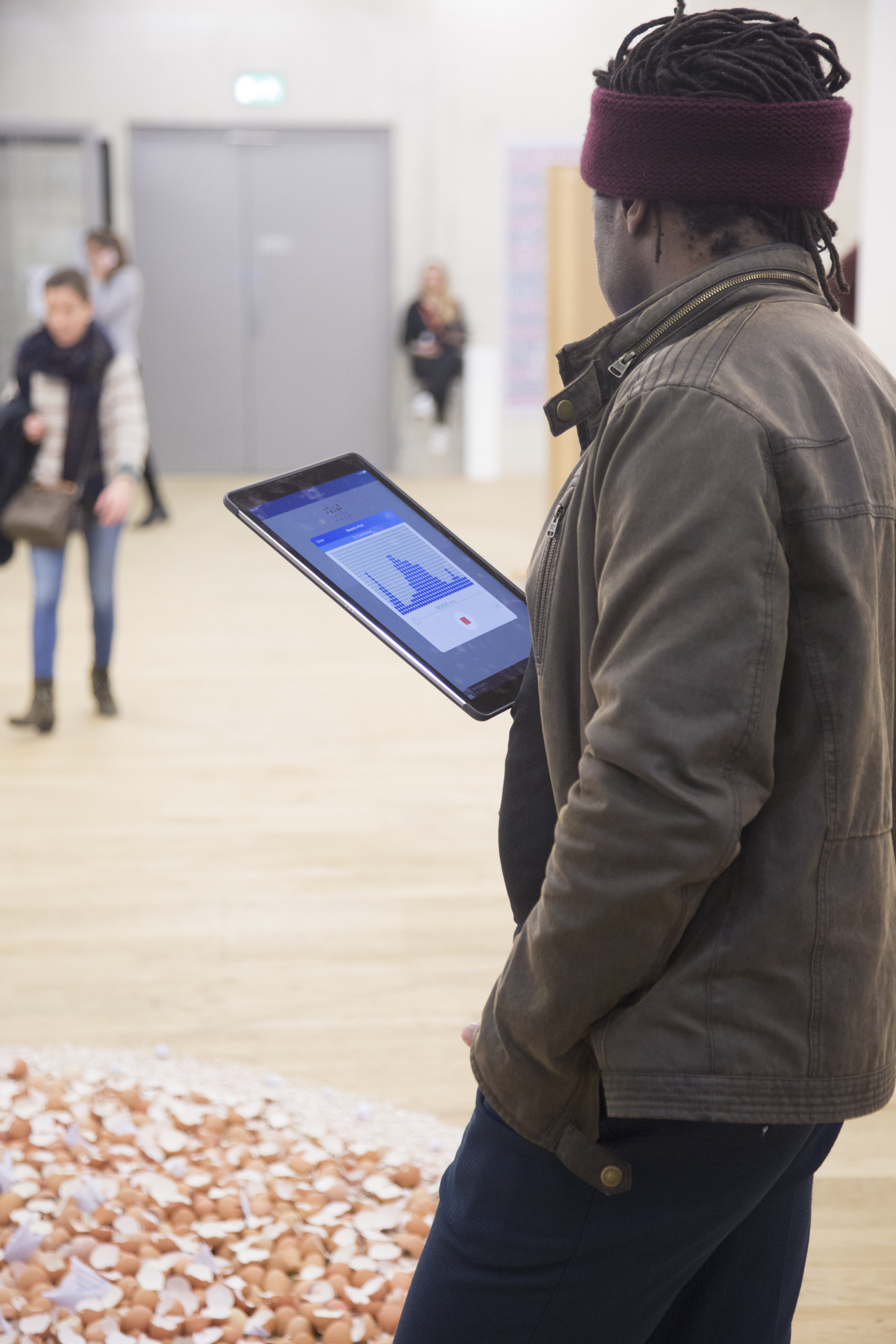 a man regards the ipad he is holding whilst standing before a floor installation of eggshells