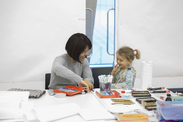 a dark haired woman sits next to a young girl in an art workshop; they are laughing and chatting and clearly are from different generations and ethnic heritages