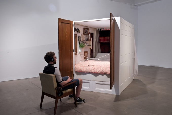 a man sits before an enclosed bed designed as an installation at baltic 39 gallery