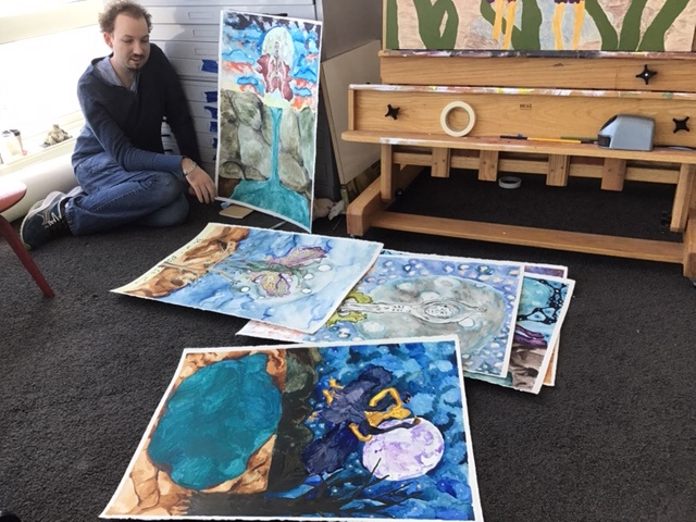 Artist sits on the floor of his studio, surrounded by his paintings.