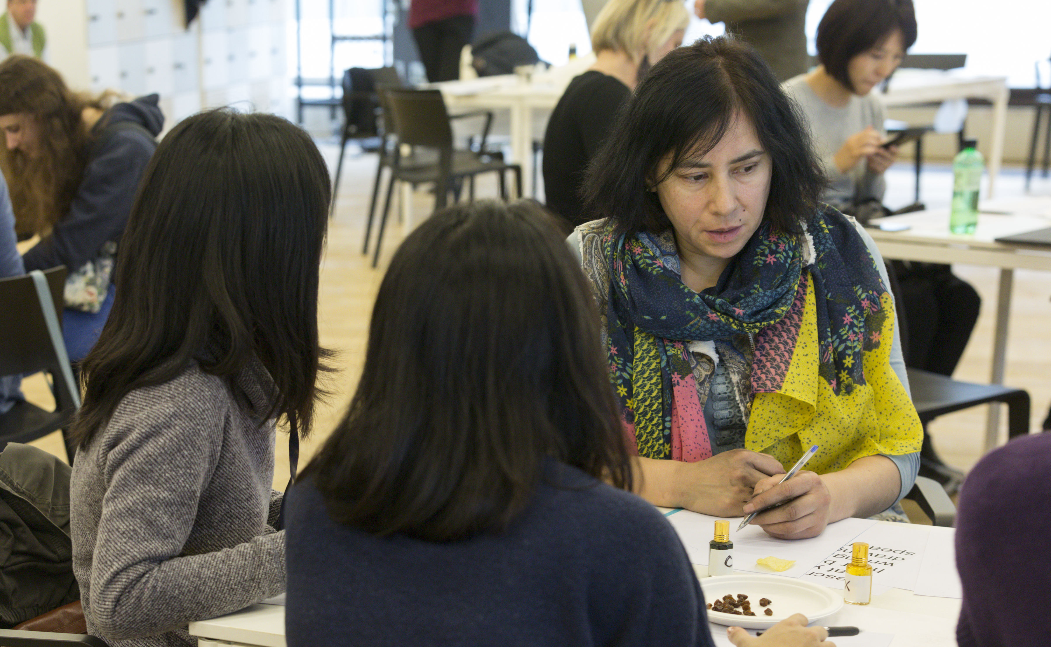 three women lean forward whilst involved in aworkshop; the man is surrounded by other people, all of whom are using art materials in an atmosphere of engaged activity