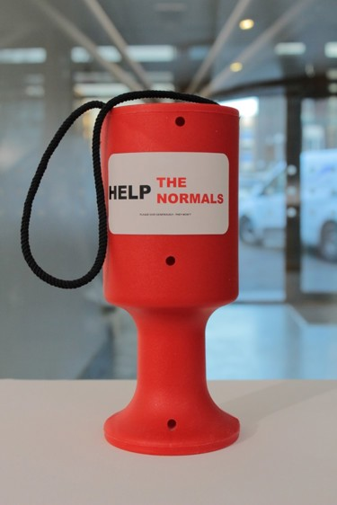 Close-up of a red charity collection box with the words 'Help the Normals' printed on it