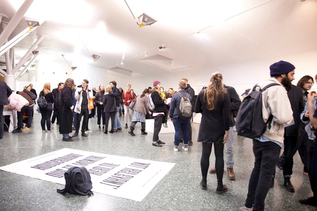 A large, crowded gallery space filled with people, with a flat, floor-based fabric work in the foreground