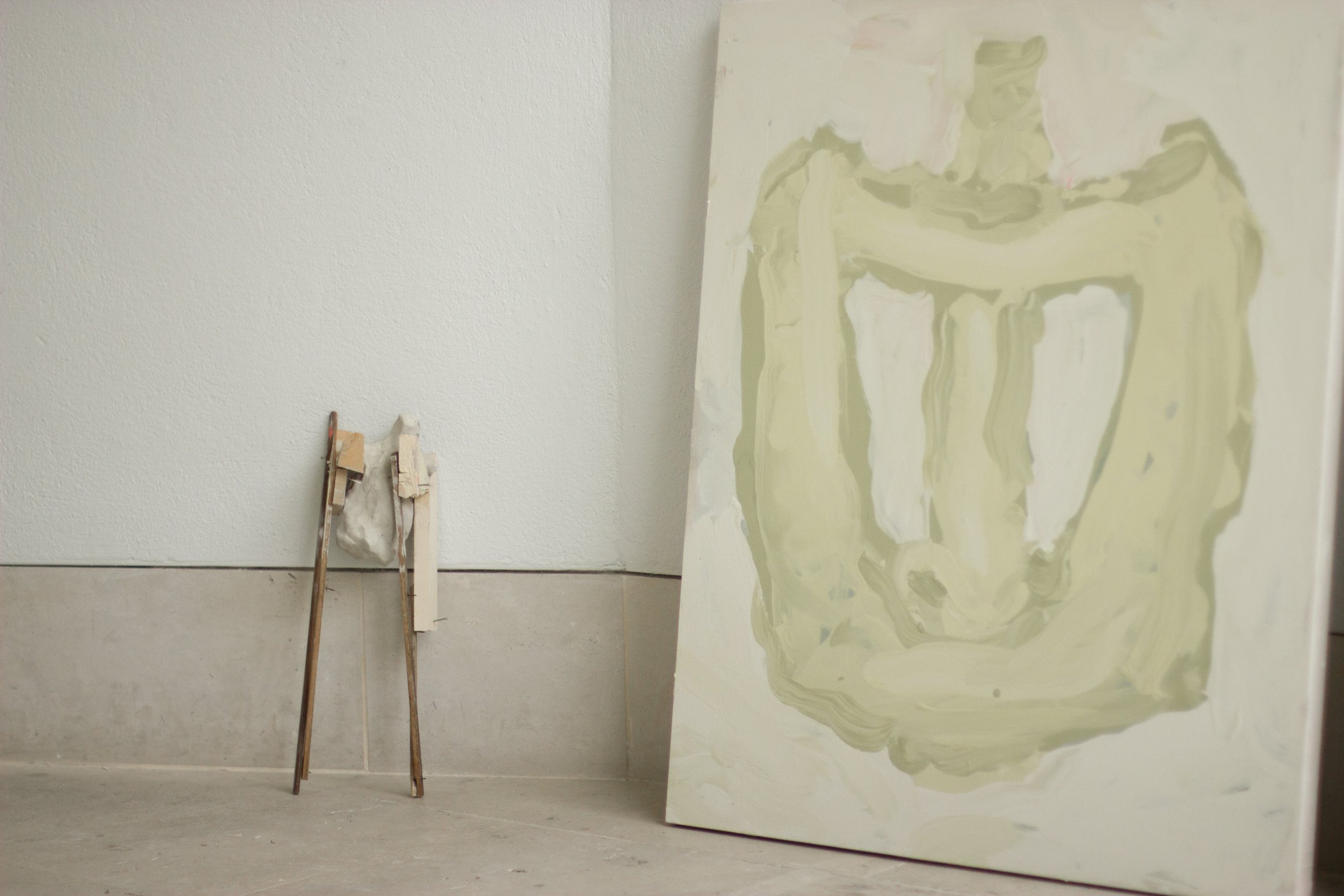 A small sculpture of clay and wood on a tile floor leaning against the light grey wall, next to a large, light green abstract painting on a canvas.