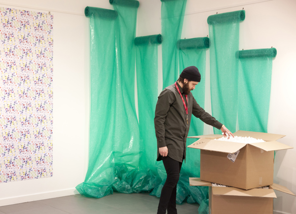 A visitor interacts with an element of the work, a box filled with polystyrene
