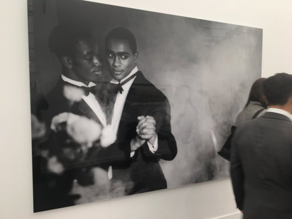 A large black and white photograph of two black men in tuxedos dancing together, on a white wall
