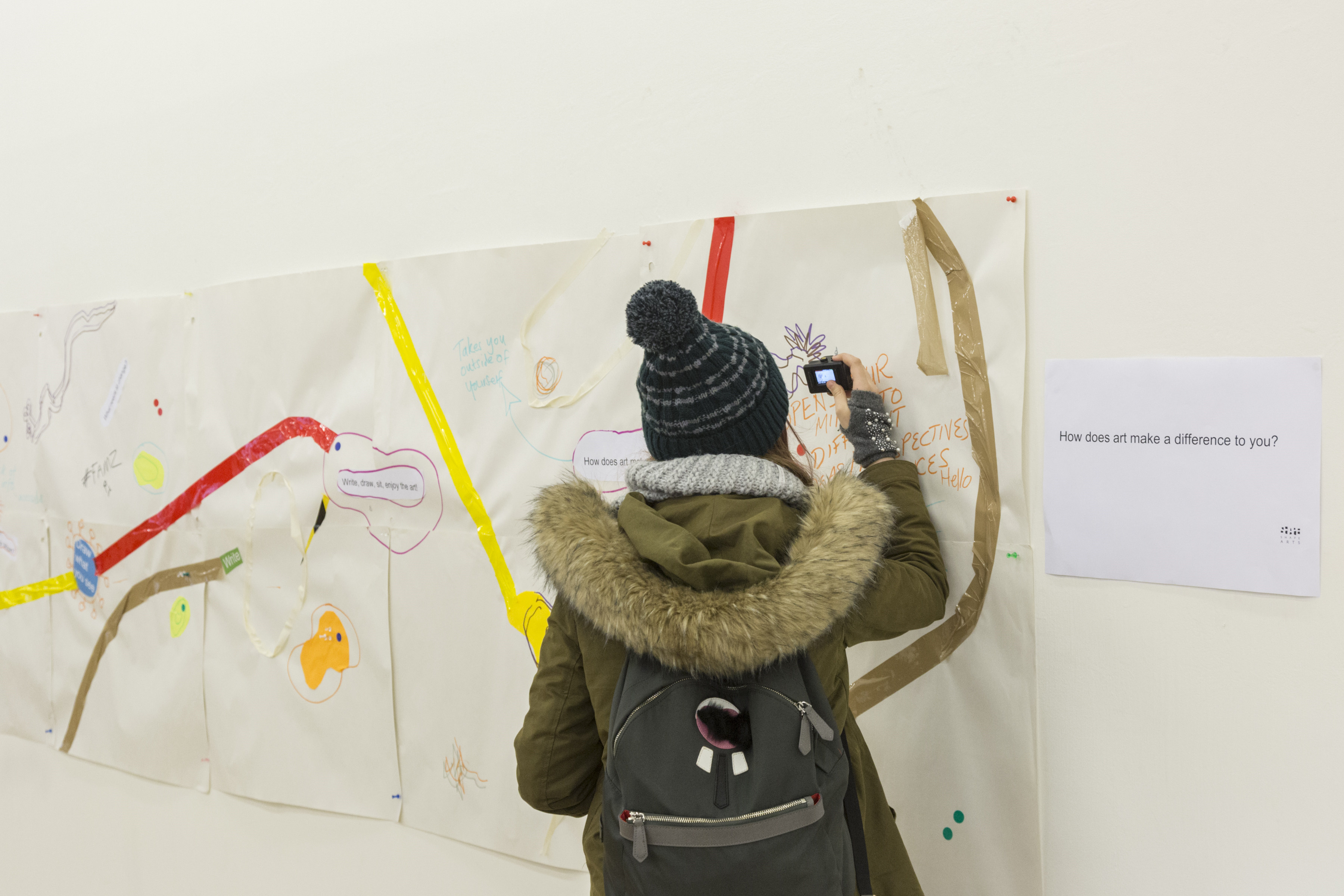a young woman with her back to us scrawls on a wall of other messages and drawings made by the public at tate exchange