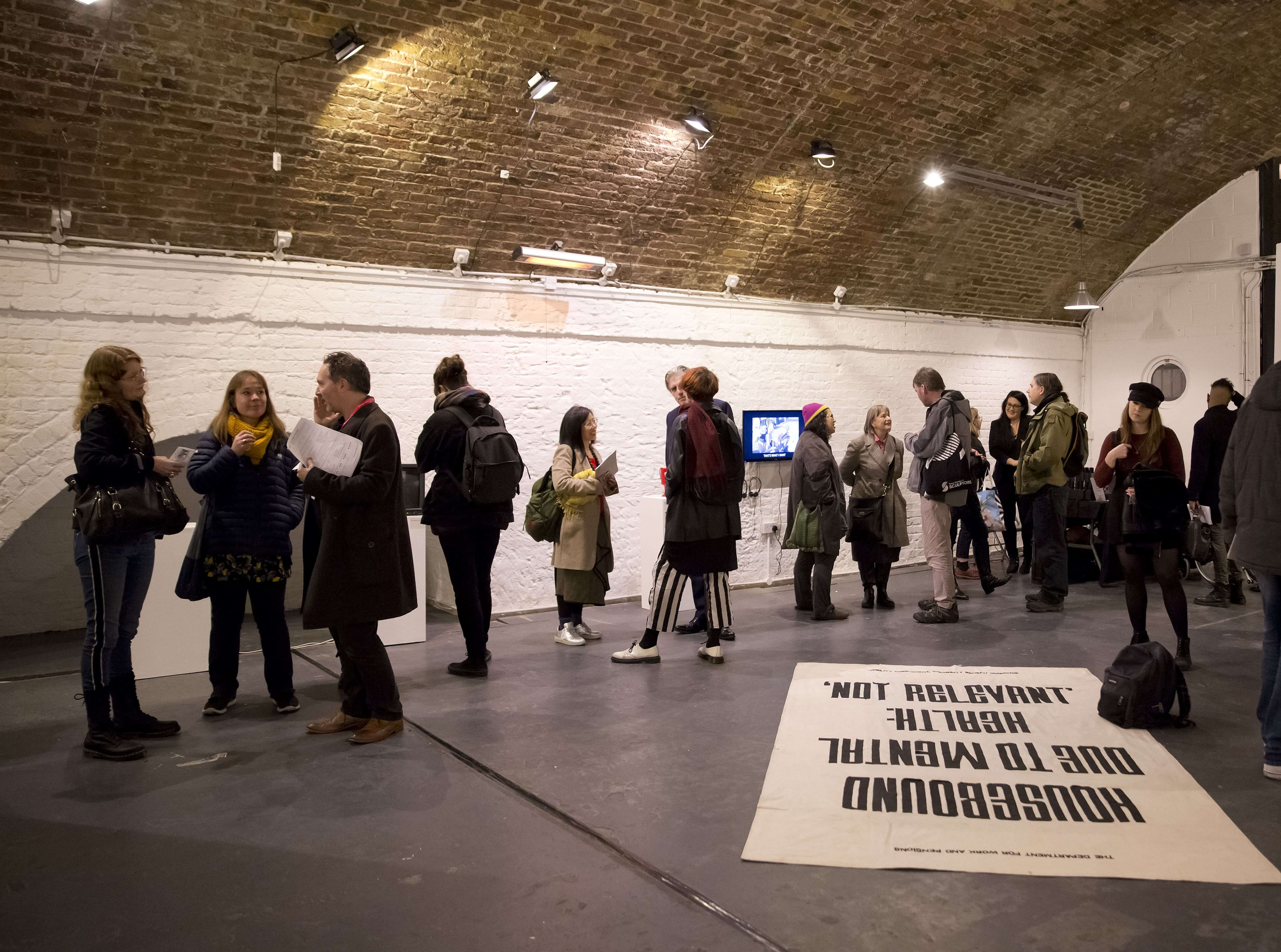 Crowd along side of room chatting to each other at art exhibition Shape Open Retrospective, Hoxton Arches, 2018