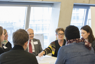 people grouped around a table, taking part in focussed discussion