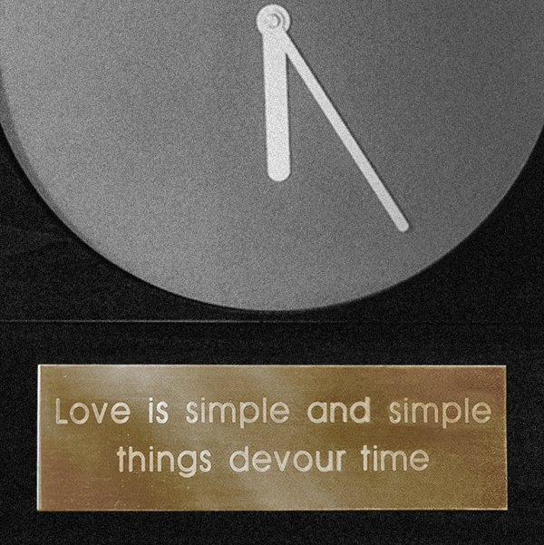 This image is cropped to present the bottom semicircle of a minimalist analogue clock with silver hour and minute hands on a plain grey background. Underneath the clock a gold plaque has the following words etched; 'love is simple and simple things d