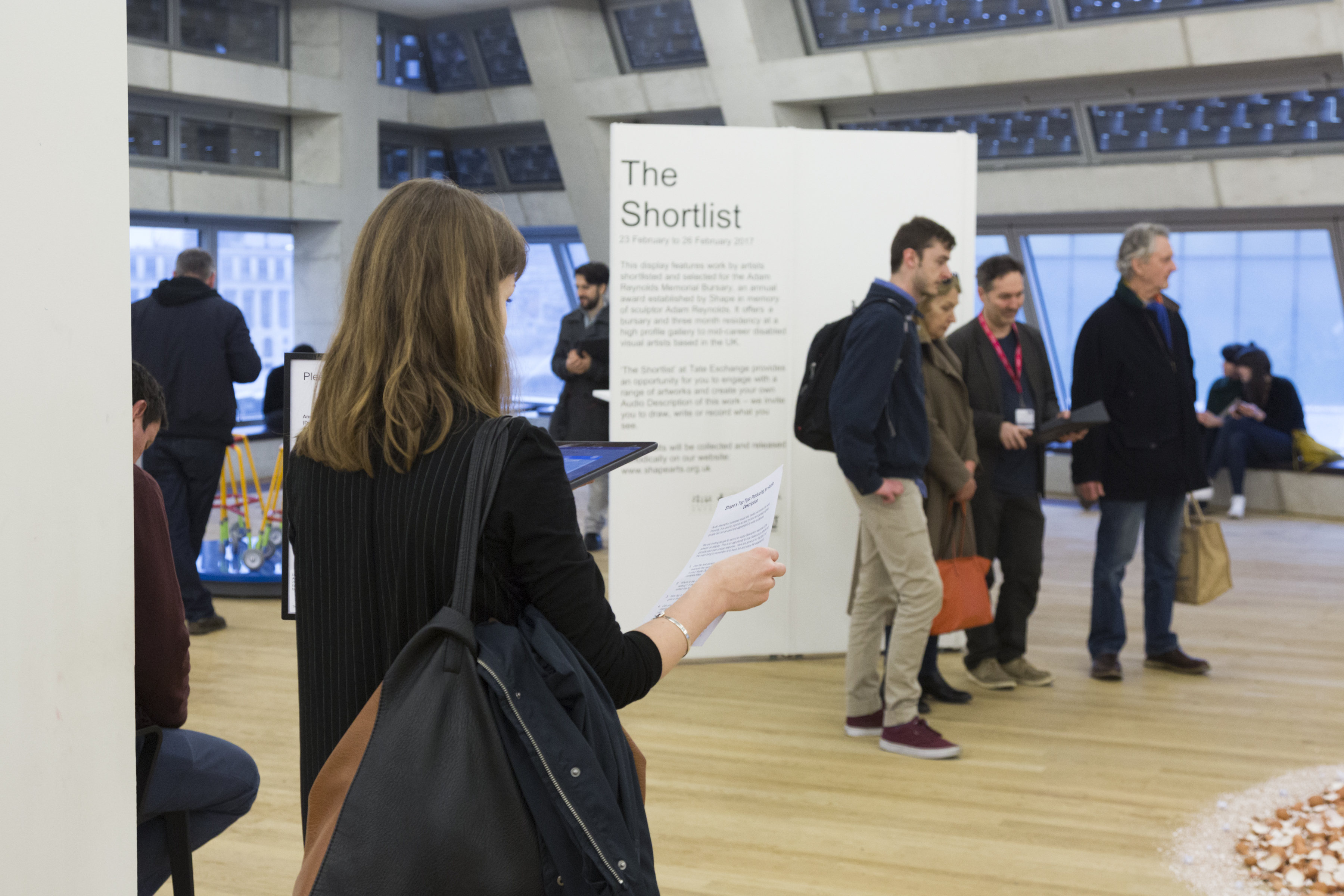 people looking at the Shortlist art disaply at Tate exchange, some of whom are making audio descriptions of the work on ipads