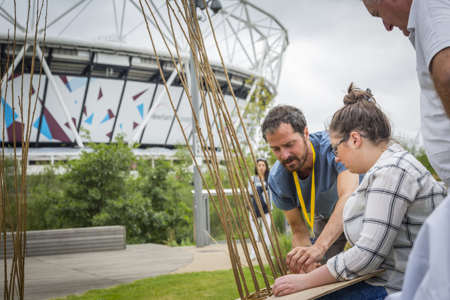 Three people in a park weaving willow in front of a stadium