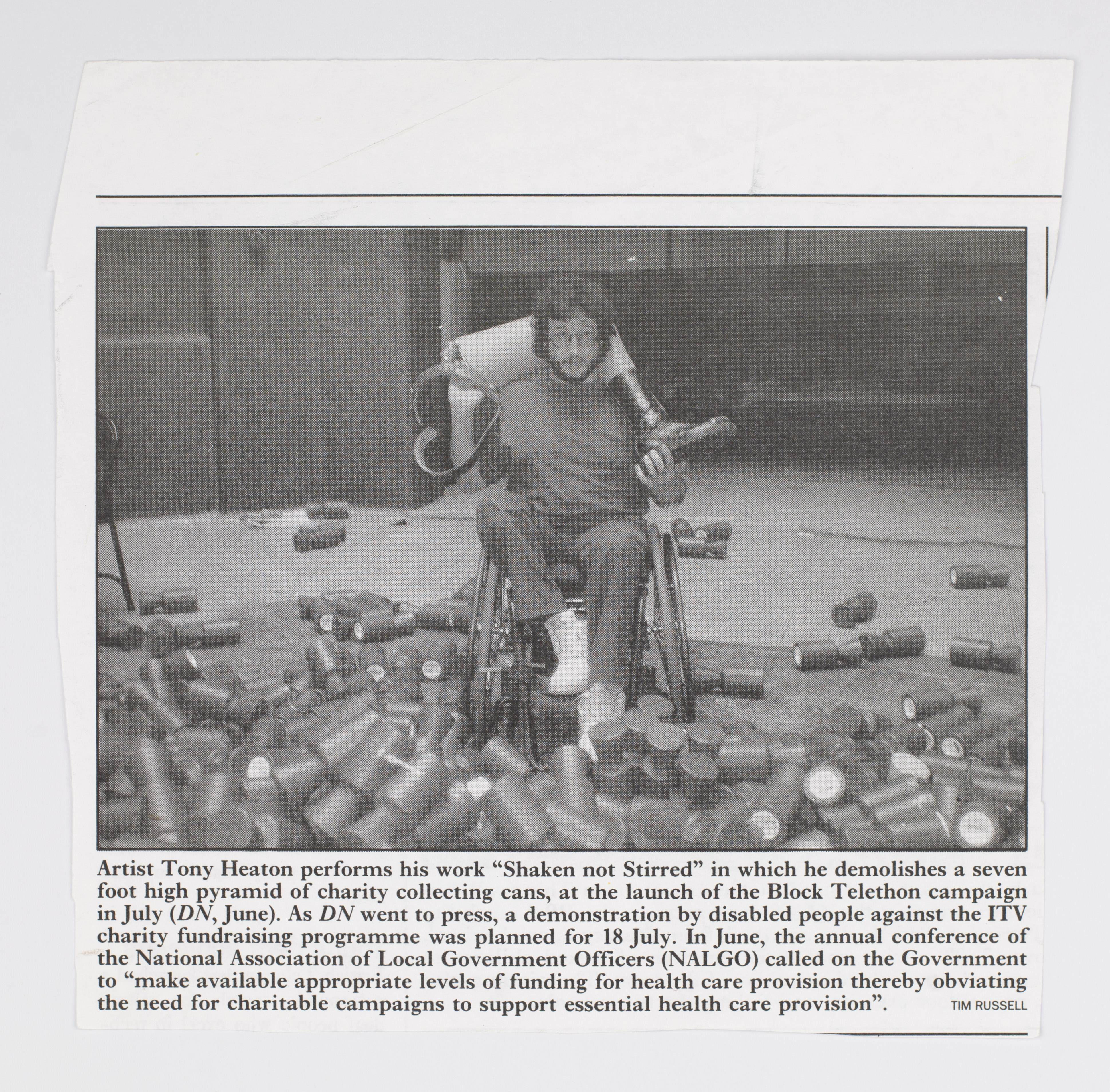 Black and white newspaper image of a young white man sitting in a wheelchair with a prosthetic leg slung over his shoulders. He is surrounded by knocked-over charity collecting cans