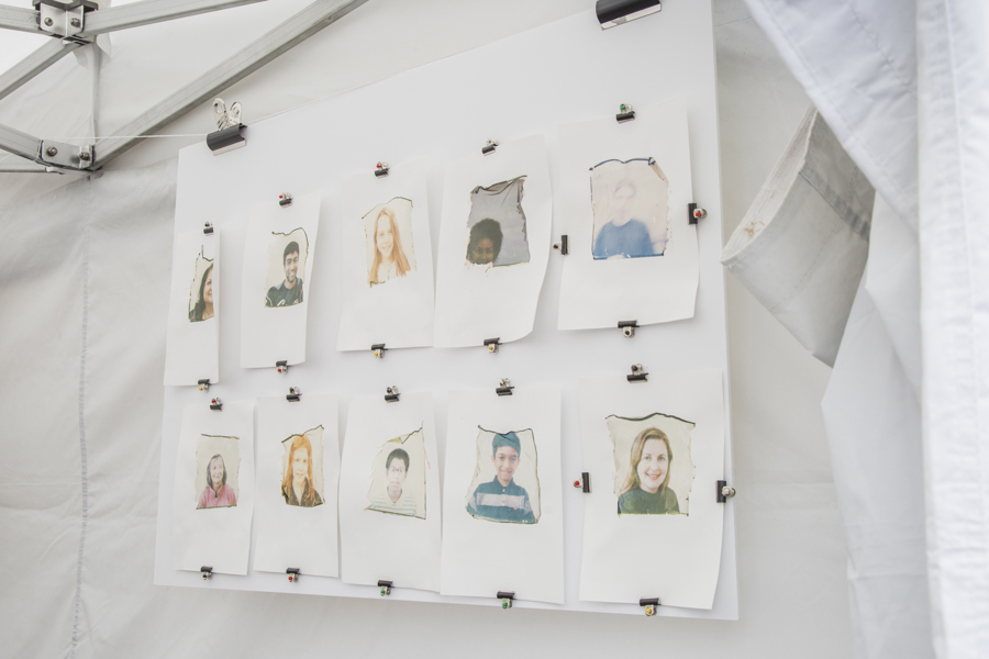 Two rows of small portrait photographs of people pegged to a line against a white background