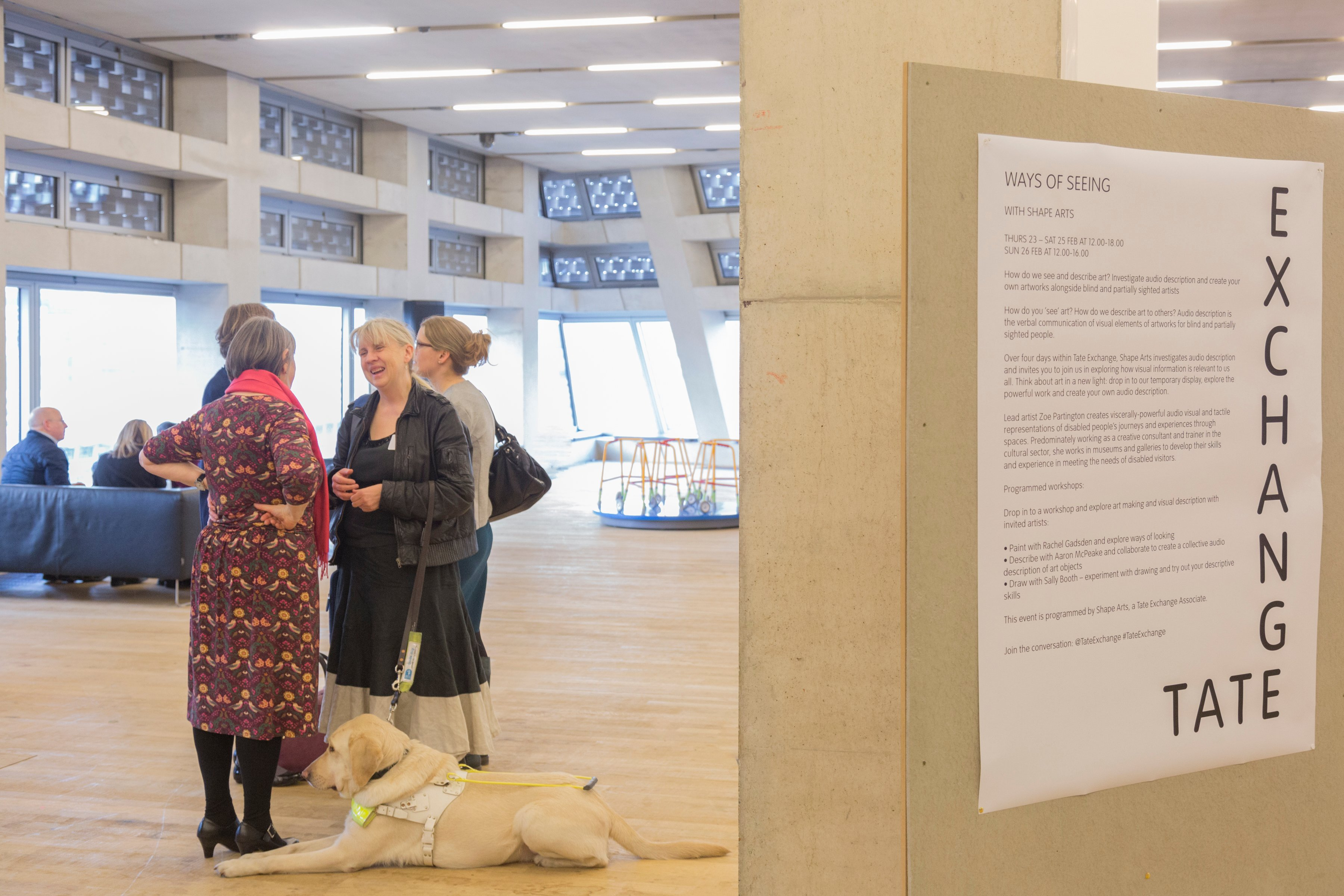 two women in conversation at tate exchange, one with an assistance dog