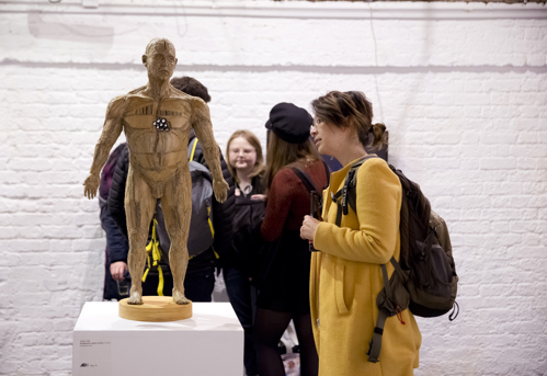 woman views a cardboard sculpture of a male figure